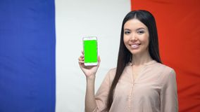Dama pokazuje smartphone z zieleń ekranem, francuz flaga na tle, podróży app zdjęcie wideo