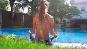 Dama relaksuje obsiadanie w joga pozie basenu zadka widokiem zdjęcie wideo