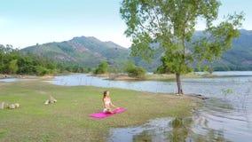 Dama relaksuje w lotos pozie przy kamienia ogródem przeciw wzgórzom zbiory wideo