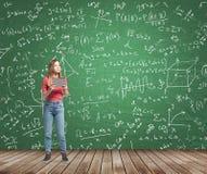 Dama rozpamiętywa o skomplikowanym matematyka problemu Formuły i wykresy rysują na zielonym chalkboard Zdjęcia Royalty Free