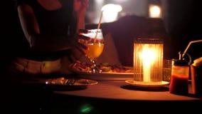 Dama stawia szkło sok pomarańczowy na kawiarnia stole z gościem restauracji zbiory