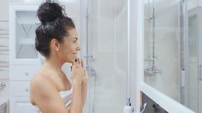 Dama stosuje twarzową śmietankę na jej twarzy przed lustrem w łazience zbiory wideo