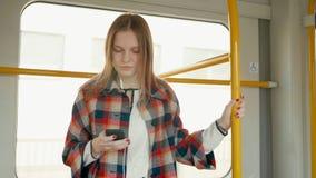 Dama używa smartphone i słuchawki w pociągu w ranku podczas gdy podróżujący zbiory