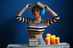 Dama w błękitnej peruce pozuje z książką na jej głowie z bliska Być może Obrazy Royalty Free