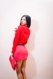 Dama w czerwieni: piękna, kusicielska brunetki kobieta stoi w czerwieni sukni z torebką, patrzejący kamerę nad ramieniem Zdjęcie Royalty Free