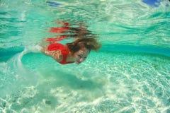 Dama w czerwonym pływanie sukni wody morza pikowaniu Zdjęcia Royalty Free