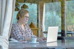 Dama wyszukuje internet na Przenośnym komputerze w kawiarni obraz royalty free