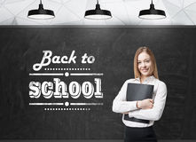 Dama z czarną falcówką myśleć o przyszłościowym akademickim roku Słowa: 'z powrotem szkoła' napisze na czarnym chalkboa Zdjęcia Royalty Free