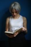 Dama z srebnym włosianym czytaniem książka i świeczki z bliska niebieska tła Fotografia Stock