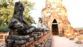 Damage Buddha statue, have blur on old wall brick gate arch back. Ground , focus on Buddha statue,  Thailand Stock Photography