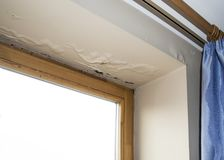 Damage caused by moisture on a ceiling. Water damaged ceiling next to window stock photo