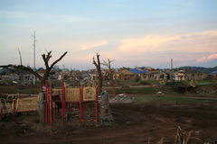 Damage after an F5 tore through Moore Oklahoma. A destroyed child's playground at sunset with clean up from the tornado in the background Royalty Free Stock Images