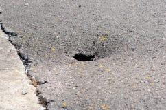Damaged asphalt - pot hole. Damaged asphalt big hole in it Royalty Free Stock Photography