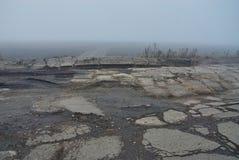 Damaged asphalt road with potholes in fog Royalty Free Stock Image