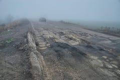 Damaged asphalt road with potholes in fog Stock Photo