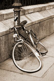 Damaged bicycle locked to an iron pillar Royalty Free Stock Images