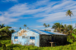 Damaged Blue Building in Green Lush Clearing Stock Photo