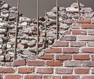 Damaged Bricks. A brick wall with part of it crumbling and fallen down, revealing the center of the wall with cement, bricks, and the metal structural beams Stock Photo