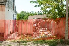 Damaged broken and demolished house with collapsed roof surrounded with orange safety net barrier for construction sites stock images