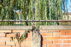 Damaged and broken red brick wall with grunge rusty iron fence close up stock photos