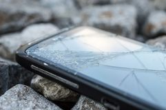Damaged and broken Screen Of a Cell phone. Damaged and broken touch Screen Of a Cell phone on rocks royalty free stock photo