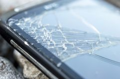 Damaged and broken Screen Of a Cell phone. Damaged and broken touch Screen Of a Cell phone on rocks royalty free stock images