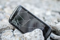 Damaged and broken Screen Of a Cell phone. Damaged and broken touch Screen Of a Cell phone on rocks stock photography