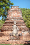 Damaged Buddha statue and ruined chedi at Wat Phra Si Sanphet, A Royalty Free Stock Photography