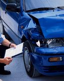 Damaged car. Surveyor at a blue damaged car after an accident Stock Photos