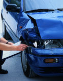 Damaged car. Expert evaluating damage on a car Royalty Free Stock Image