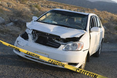 Damaged Car Behind Warning Tape. At an accident scene Royalty Free Stock Image