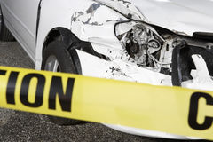 Damaged Car Behind Warning Tape. Closeup of a cropped damaged car behind warning tape at an accident scene Stock Photography
