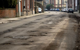 Damaged car road with a lot of cracks Stock Photos