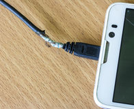 Damaged Charging of mobile phone on wood background. Stock Photography