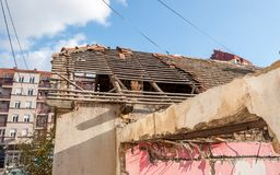 Damaged and collapsed roof tiles after aftermath earthquake or hurricane on the old ruined domestic house with broken windows sele royalty free stock photography