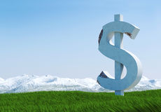 Damaged concrete dollar sign statue isolated on grass meadow with snowy mountain and blue sky as background Stock Images