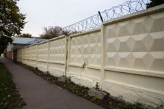 Damaged concrete fence with barbed wire. Moscow stock photo