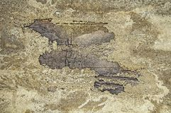Damaged concrete with splits. Gray, yellow, brown textured background. Metal rod and wire are visible in the hole stock photo