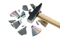 Damaged data. Broken compact disk with a hammer isolated over white Royalty Free Stock Photo