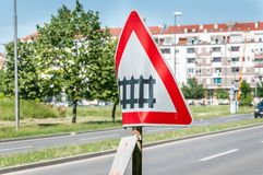 Damaged and distorted railway sign with railroad crossing road symbol signalization in the city.  Stock Photos