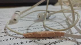 A damaged earpices attached with tape. Damaged earpices attached with duck tape lying on written paper , earpiece s seems old and little bit blury Stock Photography