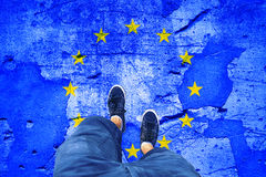 Damaged Eu flag with a man. Top view of a man standing on damaged cracked cement floor painted with European Union flag. Point of view perspective used Royalty Free Stock Photos