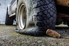 Detail of a flat black offroad tire on a offroad truck vehicle. Damaged flat offroad tire on a road royalty free stock photography
