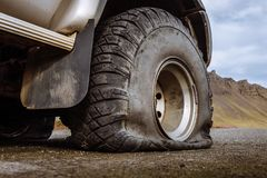 Damaged flat offroad tire on a road. Damaged flat off-road tire with a dirty dust protector, car standing on a road near mountains during cloudy day stock photos