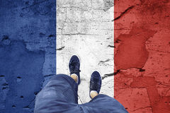 Damaged France flag with a man. Top view of a man standing on damaged cracked cement floor painted with France flag. Point of view perspective used. Conceptual Stock Images