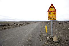 Damaged gravel road in Iceland. And traffic sign Stock Images