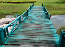 Damaged Green Bridge. Old wooden green bridge collapses down the stream Royalty Free Stock Photos