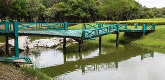 Damaged Green Bridge over stream in the Park Stock Image