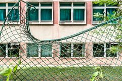 Damaged green metal wire fence distorted and broken. Damaged and collapsed green metal wire fence distorted and broken on the wall Stock Photography