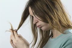 Damaged hair. Woman with worried look on her face looking at the tips of her dry, damaged hair Royalty Free Stock Images